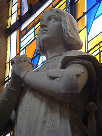 Picture of a statue of Joan of Arc with hands clasped inside a church in Blois