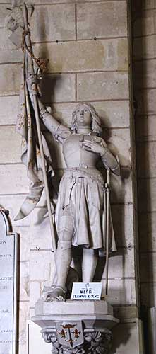 Picture of a statue of Joan of Arc with sign saying Merci Jeanne D Arc inside a church in France